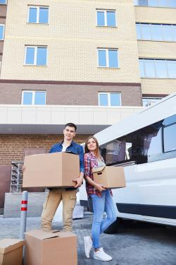 young couple moving to apartment building